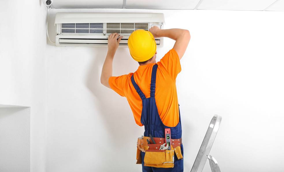 An image of a man fixing an air conditioner.